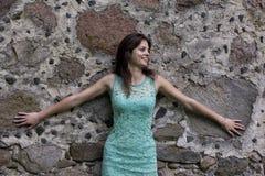 短的礼服的女孩在废墟背景站立  免版税图库摄影