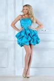 短的蓝色礼服的美丽的白肤金发的女孩。 免版税库存照片