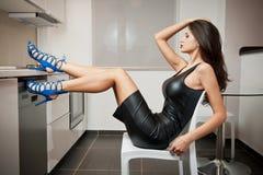 短的紧的适合皮革礼服和蓝色鞋子摆在的完善的身体妇女在一个现代厨房里放松了 肉欲的妇女侧视图  免版税库存照片