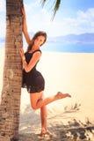 短的黑礼服的深色的女孩在棕榈赤足倾斜 库存图片