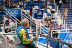 短艰苦跋涉速滑的XXII冬奥会志愿者 库存照片