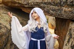 矮子服装的女孩在岩石附近 免版税库存照片