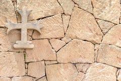 石发怒垂悬在一个石墙上,背景 库存照片