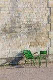 石墙和两把绿色椅子在Tuileries从事园艺(垂直) 库存照片