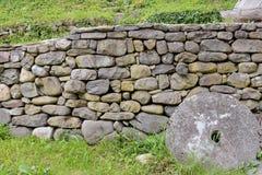 石墙和绿草在后院 免版税库存照片