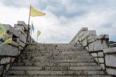 石墙楼梯有栏杆和旗子的在多云afterno 免版税库存照片