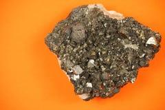 石墨矿石与不规则的纹理的块形成整个片断,在橙色纸背景的射击 免版税图库摄影