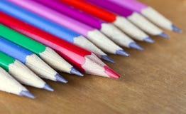 石墨铅笔连续说谎,一支铅笔有锋利的红色核心和提出的,小深度 免版税库存照片