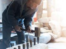 石头制造者的雕刻家触击与在w的一把重的锤子 免版税库存照片