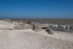 石头和具体块在风平浪静的岸在一个清楚的夏日 免版税库存照片