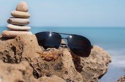 石头和太阳镜金字塔在一块石头在一个螃蟹旁边在蓝色海的背景 库存图片