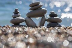 石头和小卵石堆、和谐和平衡,在海岸的三个石石标与在背景的海浪 库存照片