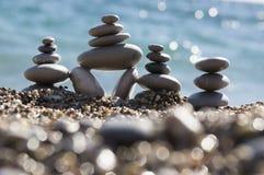 石头和小卵石堆、和谐和平衡,在海岸的三个石石标与海浪 免版税库存图片