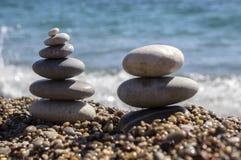石头和小卵石堆、和谐和平衡,在海岸的两个石石标 图库摄影