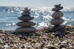 石头和小卵石堆、和谐和平衡,在海岸的两个石石标 库存照片