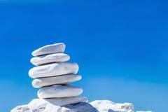 石头在克罗地亚平衡,在蓝色海运的小卵石栈。 图库摄影