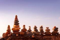 石头在日落天空的背景平衡在海滩的 免版税库存照片