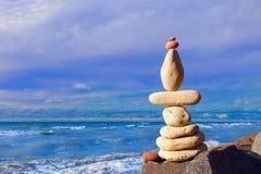 石头在日落天空的背景平衡在海滩的 库存照片