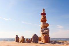 石头在日落天空的背景平衡在海滩的 免版税库存图片