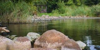 石头在有一个小树荫处的湖 库存照片