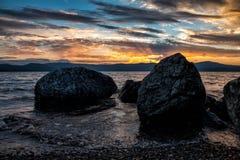石头大块在湖的岸的反对日落的背景的 免版税库存图片