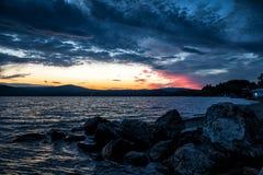 石头大块在湖的岸的反对日落的背景的 库存照片