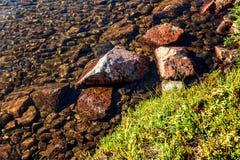 石头岸,清楚的水,绿草 免版税库存照片