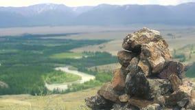 石头金字塔反对一个谷的背景的在山和一条蜿蜒的河 大横向山山 股票视频
