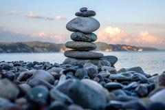 石头金字塔在一个有卵石花纹的海滩的 免版税库存照片