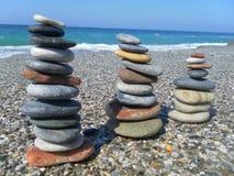 石头金字塔在海滩的反对海和天空 免版税库存图片