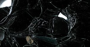 石打破的玻璃镜框反对黑背景,慢动作4K的 股票录像