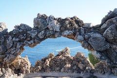 石曲拱有海视图和小船踪影 免版税图库摄影