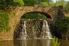 石桥梁和瀑布在Reynolda庭院里 库存照片