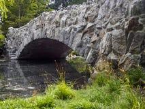 石桥梁旁边透视在水的在信标岗公园 库存照片