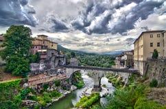 石桥梁连接一个古老村庄的双方在clou下 库存照片
