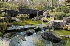 石桥梁风景在庭院小河的 免版税库存照片