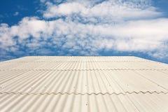 石棉反对蓝天的石板屋顶 免版税库存照片