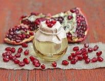 石榴在瓶的菜籽油在红色木背景 库存图片