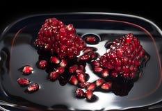 石榴水多的种子在自己的汁液的 关闭反对黑暗的背景 免版税库存图片