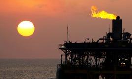 石油平台和火光在日落 库存图片