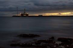 石油平台和风轮机在日落 免版税库存图片