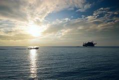石油平台在日落的海 库存图片