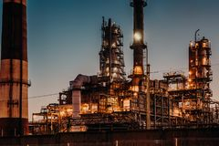 石油精炼植物在与光的晚上 钢管道和烟囱 石油和能源业生产概念 库存图片