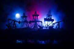 石油,小组抽油装置和明亮地被点燃的工业站点的油泵抽油装置能量工业机器在晚上 定调子 Backgrou 免版税库存图片
