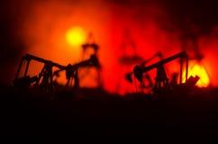 石油,小组抽油装置和明亮地被点燃的工业站点的油泵抽油装置能量工业机器在晚上 定调子 Backgrou 免版税库存照片
