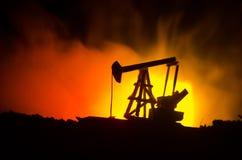 石油,小组抽油装置和明亮地被点燃的工业站点的油泵抽油装置能量工业机器在晚上 定调子 Backgrou 图库摄影
