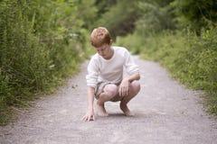 石渣道路的乡村男孩 库存图片