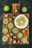 石灰切开了成在一个切板的切片有冰的 凉快的刷新的照片用柑橘水果 顶视图 免版税库存照片