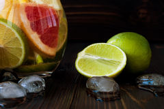 石灰和冰接近在黑暗的木桌上 免版税库存图片