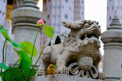 石狮子泰中雕塑细节和在黎明寺佛教寺庙的泰国艺术建筑学在曼谷 免版税库存照片